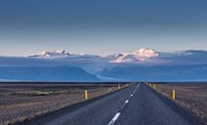 Empty-road-leading-to-snow-covered-mountains-Iceland-101313188A733BDD